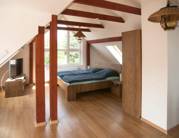 Offene Wohnfläche mit Bett in der Dachgeschosswohnung