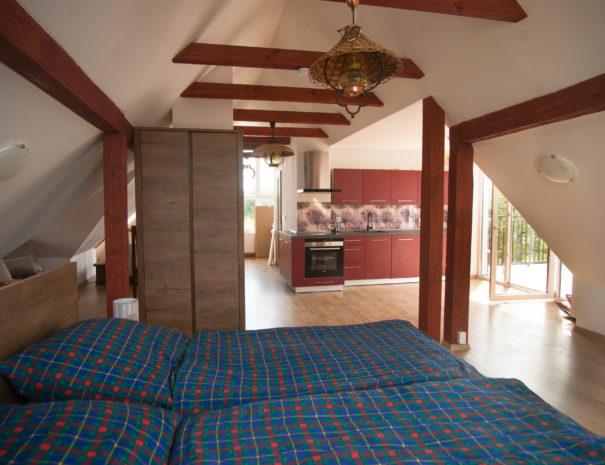 Bett und offene Wohnfläche in der Dachgeschosswohnung