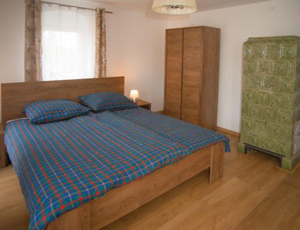 Bett mit Schrank und altem Kaminofen im 1. Geschoss