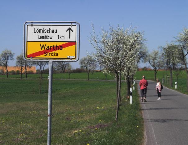 Ortsschild Wartha mit Straße und Obstbäumen daneben.